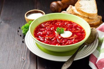 Borsch - traditional Ukrainian and Russian beetroot soup on dark wooden background