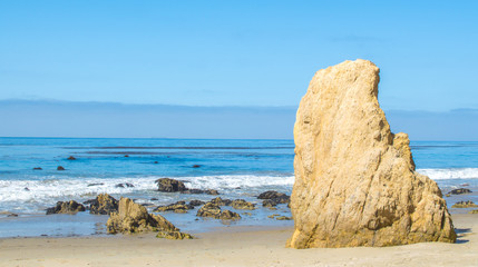 jagged rock formation on the beach at the Pacific ocean in Malibu, California on a sunny summer day