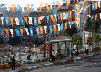 People wait for the bus under election campaign flags of the AK Party in Istanbul