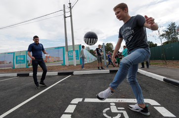 Youths play with a ball at a parking place in the setttlement of Glebovsky