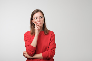 thoughtful european woman in red sweater is looking up thinking or planning. Concept of doubtful mind