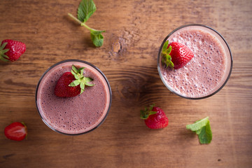 Two glasses of chocolate strawberry milkshake or cocktail on wooden table.  Strawberry chocolate smoothie with berries. Healthy drinks. overhead, horizontal