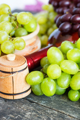 Bunches of fresh different ripe grapes and a bottle of red wine on a blue wooden textural surface. space for advertising text