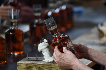 A worker applies the label and prepares a bottle of bourbon for shipment at the Buffalo Trace Distillery in Frankfort