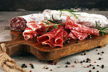 Food tray with delicious salami, prosciutto crudo,  fresh sausages and herbs. Meat platter with selection