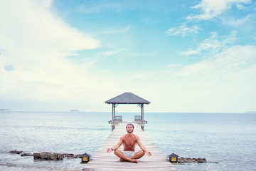 Yoga near the sea. Young man in lotus pose sitting on wooden pier. Concept of pray and meditation.