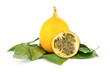 yellow Grenadilla oval fruit on a green leaf substrate, an exotic fruit with a fragrant filling