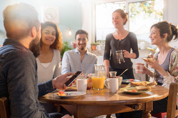 Group of multi-ethnic friends gathered around a table for breakfast