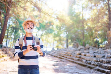 Enjoying travel. Senior smiling man with backpack holding camera on ancient sightseeing background.