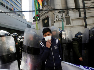 A student from the UPEA (El Alto Public University) stands next to riot policemen in La Paz