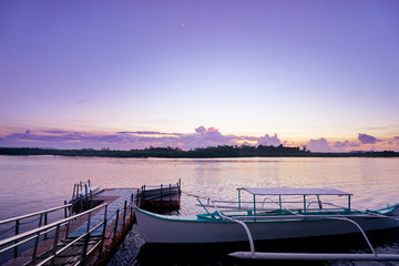 Beautiful colorful sunset on the seashore with fishing boats. Philippines, Siargao Island.