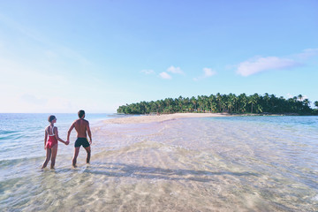 Honey moon on the sea shore. Back view of loving couple walking together on beautiful tropical white sand beach.