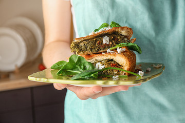 Woman holding piece of tasty pie with spinach on plate