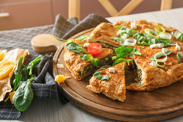 Tasty pie with spinach on wooden board