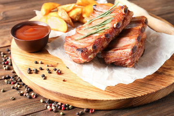 Board with delicious grilled ribs on wooden table