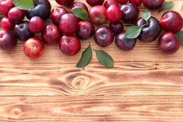 Ripe juicy plums on wooden table