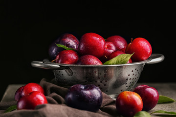 Colander with ripe juicy plums on dark background