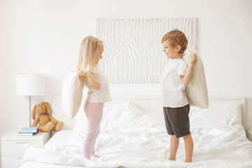 Cute children having fun on bed together