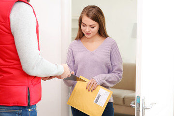 Woman signing for parcel delivery at doorway
