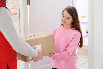 Young woman receiving parcel from courier at doorway