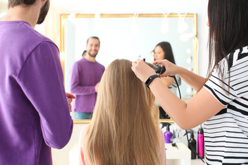 Professional hairdresser and trainee working with client in salon. Apprenticeship concept