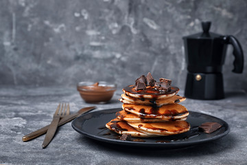 Tasty pancakes with chocolate on table