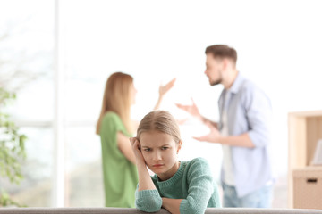 Little unhappy girl sitting on sofa while parents arguing at home