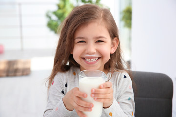 Cute little girl with glass of milk indoors