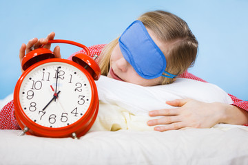 Sleeping woman wearing pajamas holding clock