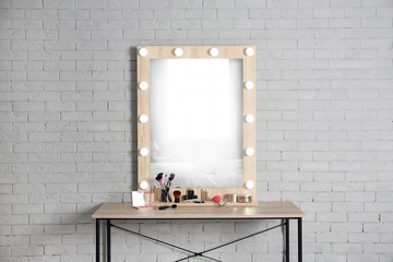 Dressing room interior with stylish mirror and set of makeup products