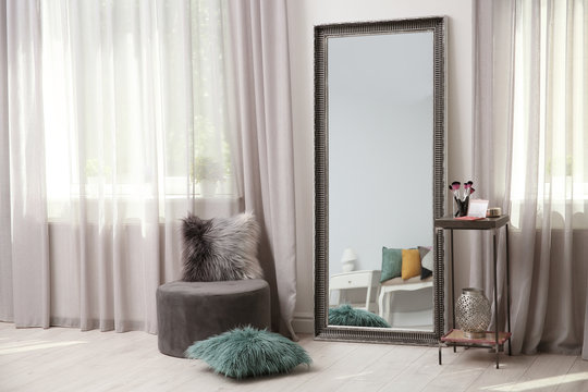 Stylish room interior with large mirror and elegant curtains