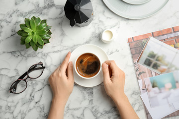 Young woman with cup of delicious hot coffee at table, top view