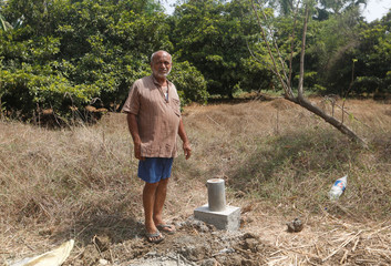 Mahendra Choudhary, a 66-year old farmer, looks on as he stands beside a bullet train construction mark laid out on his farm in Palghar
