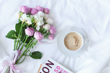 Flat lay composition with cup of coffee, beautiful flowers and magazine on fabric