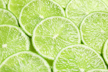 Fresh sliced ripe limes as background, closeup