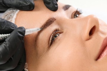 Young woman undergoing eyebrow correction procedure in salon