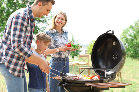 Happy family having barbecue with modern grill outdoors