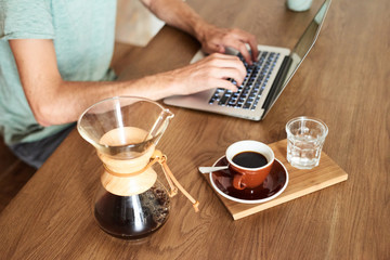 Unrecognizable businessman using laptop at table with chemex and coffee cup.