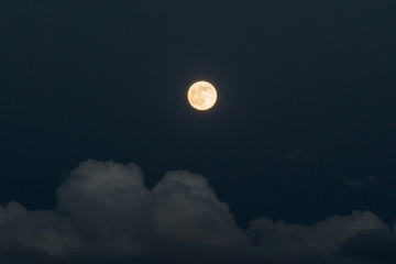 Shining bright moon in evening sky with grey clouds around