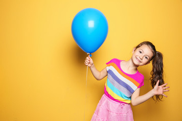 Cute girl with balloon on color background. Birthday celebration