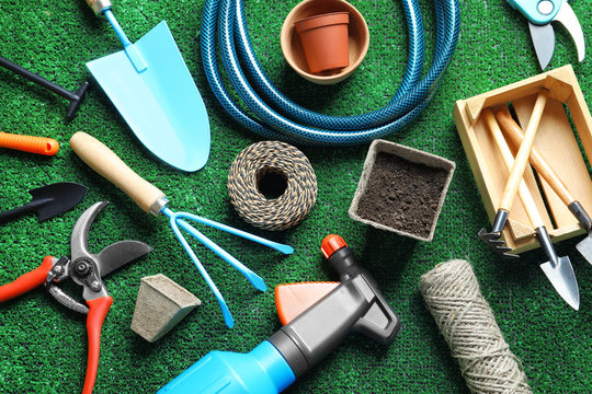 Flat lay composition with professional gardening tools on artificial grass