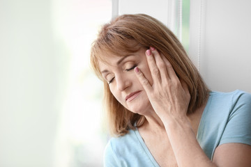 Senior woman suffering from depression near window