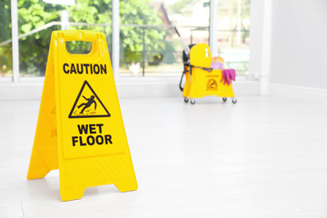 "Safety sign with phrase ""CAUTION WET FLOOR"" and mop bucket on floor, indoors. Cleaning tools"