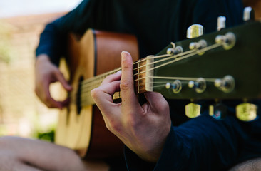 anonymous man playing acoustic guitar