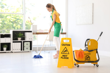 """Phrase """"CAUTION WET FLOOR"""" on safety sign, mop bucket with cleaning supplies and young woman on background"""