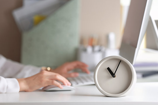 Alarm clock and blurred woman working on background. Time management