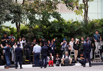 Members of the media work as security personnel keep watch near the entrance to the Capella Hotel in Singapore