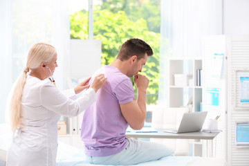 Doctor examining coughing young man at clinic