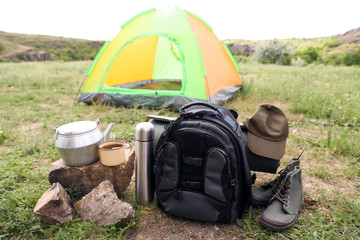 Camping gear and tourist tent in wilderness