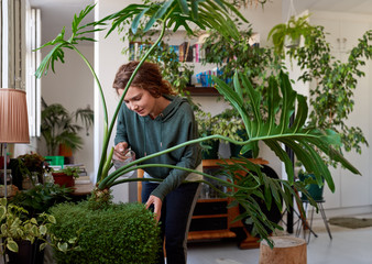 Happy free spirited woman in her plant filled apartment